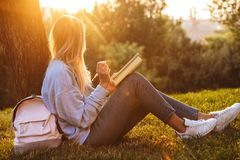 Portrait of a young girl sitting on a grass at the park. Reading a book, taking notes Stock Photos