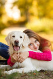 Portrait of Young girl sitting on the ground with her dog retriever in autumn scene Stock Photo