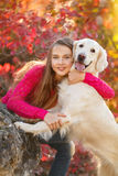 Portrait of Young girl sitting on the ground with her dog retriever in autumn scene. A beautiful woman and her dogs (Labrador retriever) posing in autumn park royalty free stock photo