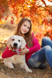 Portrait of Young girl sitting on the ground with her dog retriever in autumn scene. A beautiful woman and her dogs (Labrador retriever) posing in autumn park stock photography