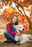 Portrait of Young girl sitting on the ground with her dog retriever in autumn scene. A beautiful woman and her dogs (Labrador retriever) posing in autumn park stock photo