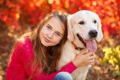 Portrait of Young girl sitting on the ground with her dog retriever in autumn scene. A beautiful woman and her dogs (Labrador retriever) posing in autumn park royalty free stock image