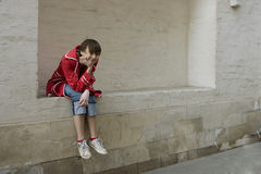 Portrait of young girl sitting at the wall Royalty Free Stock Photo