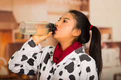 Portrait of young girl with skin problem drinking a botle of water Royalty Free Stock Image