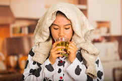 Portrait of young girl with skin problem drinking a cup of te with a grey towel in her head Stock Photography