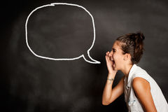 Portrait of young girl with speech bubble on chalkboard. Portrait of young girl screaming in front of chalkboard with speech bubble Stock Image
