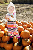Portrait of a young girl standing on pumpkin Royalty Free Stock Photography