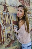 Portrait of a young girl standing by the wall with a painted graphite. Portrait of a young girl with brown hair, standing by the wall with a painted graphite Stock Photography