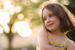 Portrait of young girl in the summer sun. Young girl smiling on a sunny day with beautiful bokeh background Royalty Free Stock Images