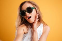 Portrait of a young girl in sunglasses taking a selfie. Portrait of a young attractive girl in sunglasses taking a selfie isolated over yellow background Stock Photography