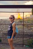 Portrait of a young girl during sunset. Glasses. In the background burns the fire.  Stock Image
