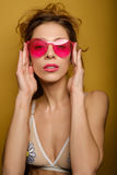 Portrait of a young girl in a swimsuit with gathered hair, holding the fingers of the arch of pink glasses and looking at the came. Ra on a yellow background Royalty Free Stock Photography