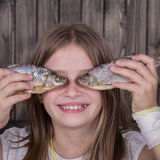 Portrait young girl together with the dried fish, close up Royalty Free Stock Images