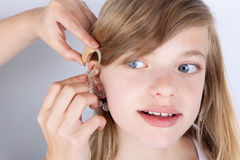 Portrait of a young girl trying hearing aids royalty free stock images