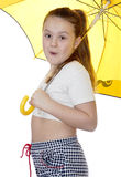 Portrait of the young girl with a umbrella on a white background. Portrait of the girl with the dismissed hair and with a yellow umbrella Royalty Free Stock Image