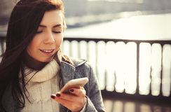 Portrait of young girl using her trendy smart phone Royalty Free Stock Image