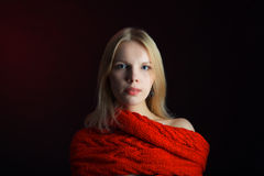 Portrait of young girl wearing red scarf on black background. Photo of young girl wearing red scarf Stock Photo