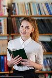 Portrait of a young girl, with a book in the library. Stock Photos