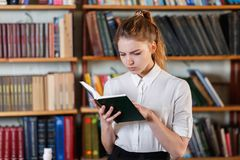 Portrait of a young girl who is reading a book in the library. Stock Photos