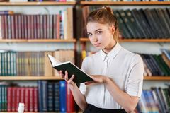 Portrait of a young girl who is reading a book in the library. Royalty Free Stock Image