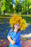 Portrait of young girl in wreath of yellow leaves. Autumn walking royalty free stock photo