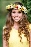 Portrait young girl in yellow dress with Flower wreath for head. Walking in park, Warm summer day. royalty free stock photography