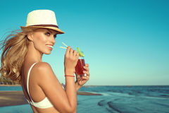 Portrait of young glam smiling blond lady in white swimming bra and panama drinking cocktail through a straw. Portrait of young glam smiling blond lady in white Royalty Free Stock Photos