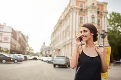 Portrait of young good-looking caucasian woman with dark hair in black dress waking around city, talking on phone royalty free stock images
