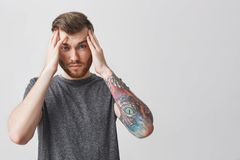 Portrait of young good-looking unhappy caucasian guy with stylish hairstyle in casual gray t-shirt holding forhead with stock image