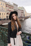 Portrait of young gorgeous brunette women with long hair standing on a river bridge in cloudy autumn day Stock Images
