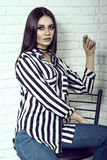 Portrait of young gorgeous dark-haired model wearing jeans, striped shirt with pockets and black choker Stock Images