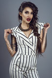 Portrait of young gorgeous dark-haired tattooed lady in striped overall and splendid necklace holding sleeves in her hands royalty free stock photography