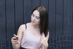 Portrait of young elegant woman outside using phone royalty free stock images