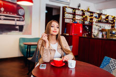 Portrait of young gorgeous female drinking coffee and looking with smile out of the coffee shop window while enjoying her leisure Stock Images