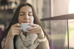 Portrait of young gorgeous female drinking cup of coffee and enjoying her leisure time alone. Portrait of young gorgeous female drinking cup of coffee and stock photo