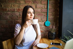 Portrait of young gorgeous female drinking tea and looking with smile out of the coffee shop window while enjoying her leisure tim Royalty Free Stock Photos