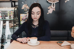 Portrait of young gorgeous girl drinking tea and thoughtfully looking out of the coffee shop window while enjoying her Royalty Free Stock Image