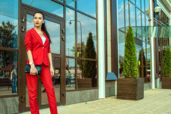 Portrait of young gorgeous lady with high pony tail in red costume and high-heeled shoes standing in front of mirrored shop window Stock Image