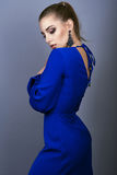 Portrait of young gorgeous model with ponytail and artistic make-up wearing electric blue open back dress and long earrings. Portrait of young gorgeous model Royalty Free Stock Photography