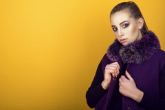 Portrait of young gorgeous model with ponytail and artistic make-up wearing trendy purple sleeveless coat with fur collar. And holding its lapel. Isolated on Stock Images