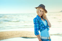 Portrait of young gorgeous blond in blue checked shirt and hat standing at the seaside, her hair blown by the wind stock photo