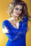 Portrait of young gorgeous sexy lady with long waved hair and provocative make-up wearing bright electric blue lace dress. With deep V neck embracing herself on Royalty Free Stock Images
