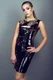 Portrait of young gorgeous slender model with ponytail and artistic make-up wearing tight-fitting sequin golden dress. Standing with the hand on her hip at the Royalty Free Stock Images