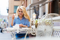 Portrait of young gorgeous tourist woman enjoying delicious cake while relaxing in coffee shop after walking outside, Royalty Free Stock Photo