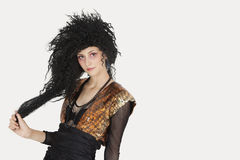 Portrait of young Goth woman with teased hair over gray background Royalty Free Stock Photo