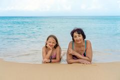 Portrait of young granddaughter and elderly grandmother look at camera posing for family picture stock images