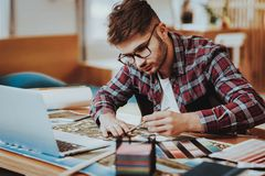 Portrait of Young Graphic Designer Works Indoors. Bearded Guy Wearing Glasses Sitting at Workplace Doing Design Project Using Laptop Looking at Palette Holding royalty free stock photo