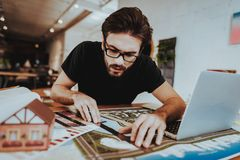 Portrait of Young Graphic Designer Works Indoors. Bearded Illustrator Wearing Glasses Sitting at Workplace Doing Design Project Using Pencil and Ruler Looking stock photos