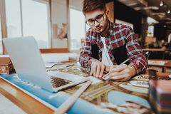 Portrait of Young Graphic Designer Works Indoors. Bearded Illustrator Wearing Glasses Sitting at Workplace Doing Design Project Using Pencil and Ruler Looking royalty free stock image