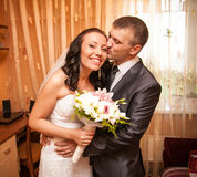 Portrait of young groom kissing bride in room Royalty Free Stock Images